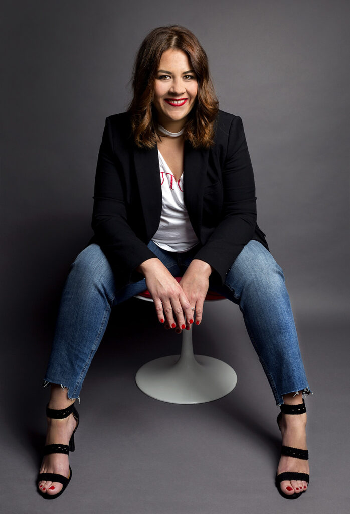 Elisabet Quesada sentada en un tamburete con un fondo oscuro
